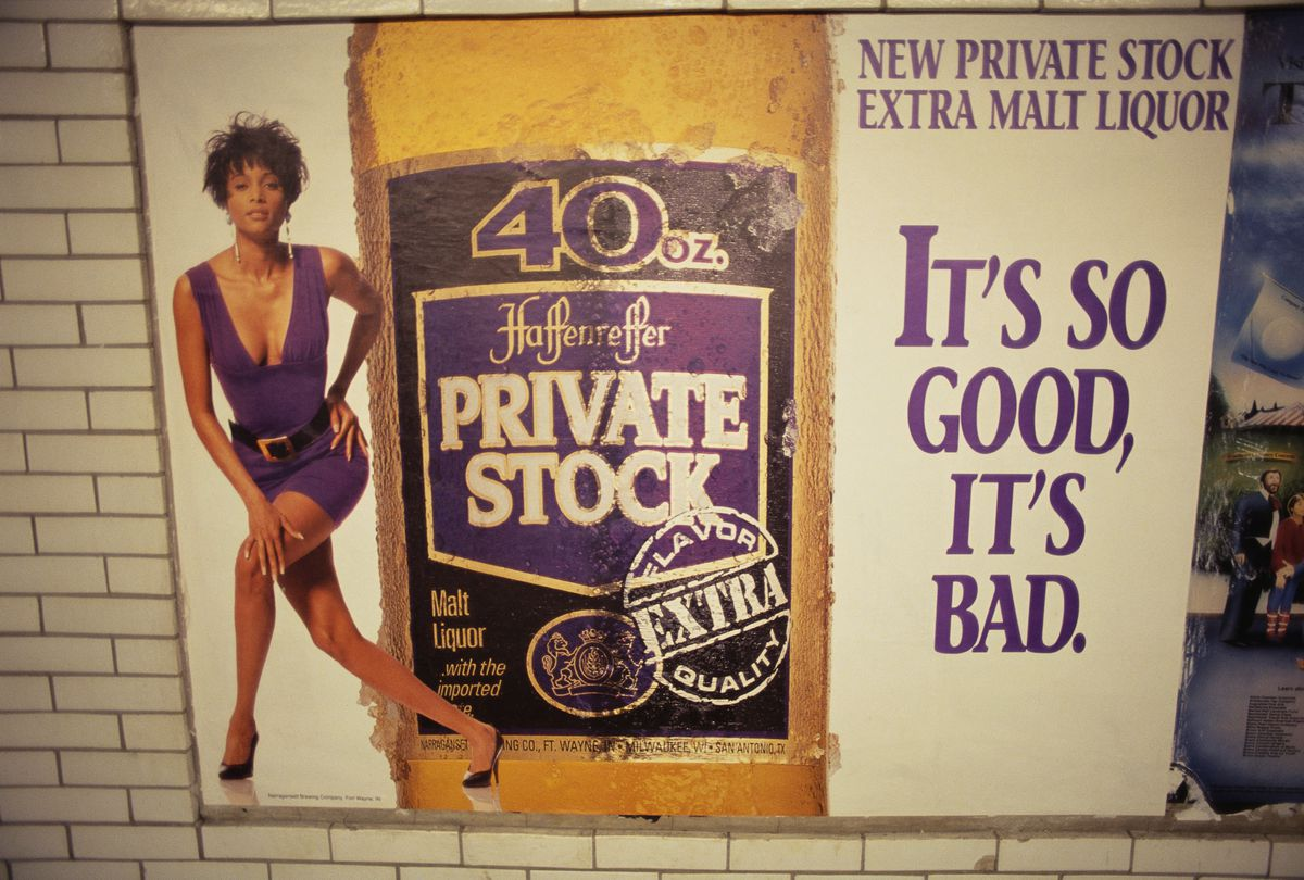 "A malt liquor ad hanging on a subway wall, with a photo of a woman in a low-cut dress, a bottle, and the tagline ""IT'S SO GOOD, IT'S BAD."""