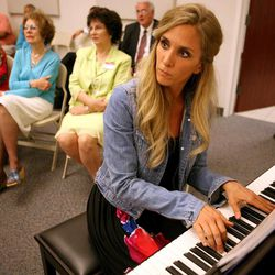 Kendra Lowe plays the piano during a memorial service for Janie Thompson, the founder of BYU's internationally touring Young Ambassadors, at the BYU multi-stake center in Provo on Saturday, June 8, 2013.