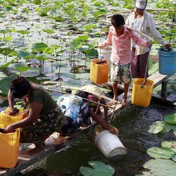 In this photo taken on April 21, 2012, local residents use plastic containers to fetch drinking water from a lake in Yangon, Myanmar. Earth Day is marked on Sunday, April 22, 2012.