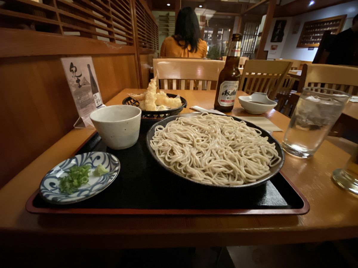A black platter holds a big bowl of buckwheat noodles, a small cup for dipping broth, and a small platter with green onions