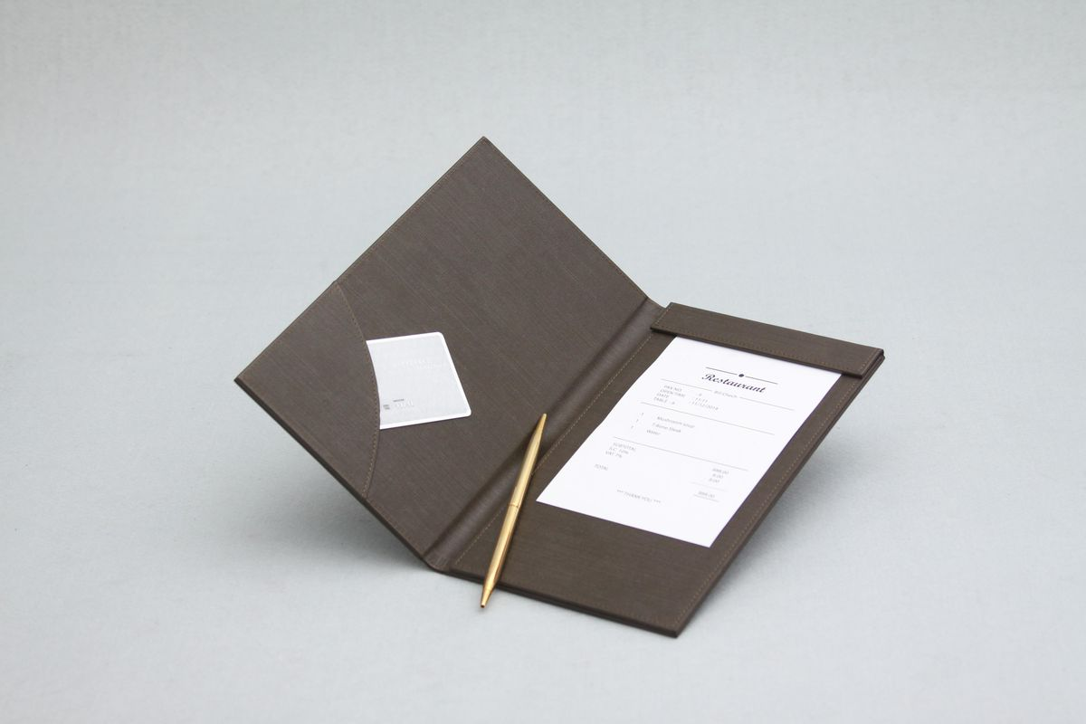 An open folder with a pen, a credit card, and a restaurant check against a blank gray background