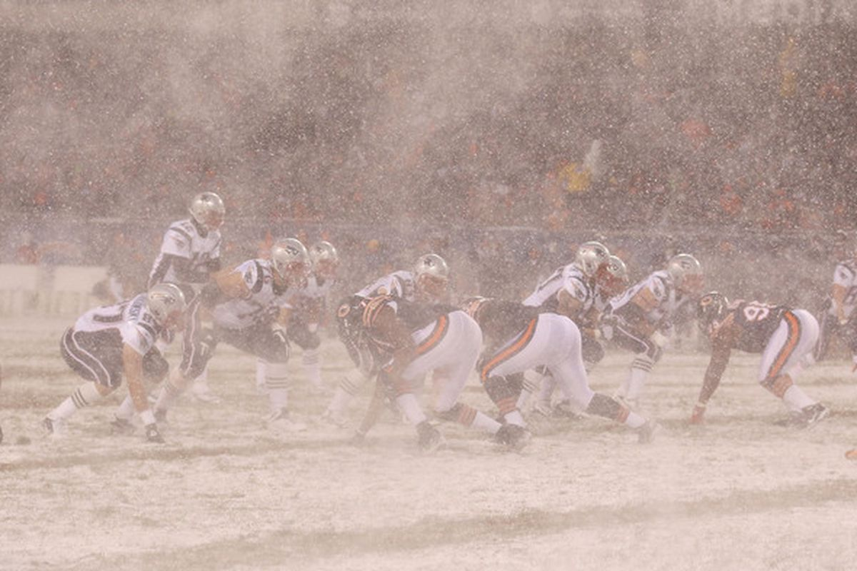 The wind swirls snow as Tom Brady #12 of the New England Patriots calls the signals against the Chicago Bears at Soldier Field in Chicago Illinois. (Photo by Jonathan Daniel/Getty Images)
