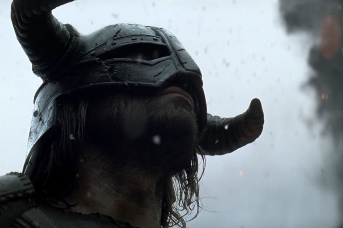 A still from the live-action Skyrim trailer shows a man in a horned helmet looking fearsome. Snow is falling. He likely smells quite bad.
