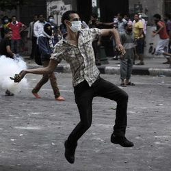 An Egyptian protester throws back a tear gas canister toward riot police, unseen, outside the U.S. embassy in Cairo, Egypt, Thursday, Sept. 13, 2012. Tens were injured in clashes in front of the U.S. embassy in Cairo, the state TV reported on Thursday, quoting Egypt's Health Ministry.