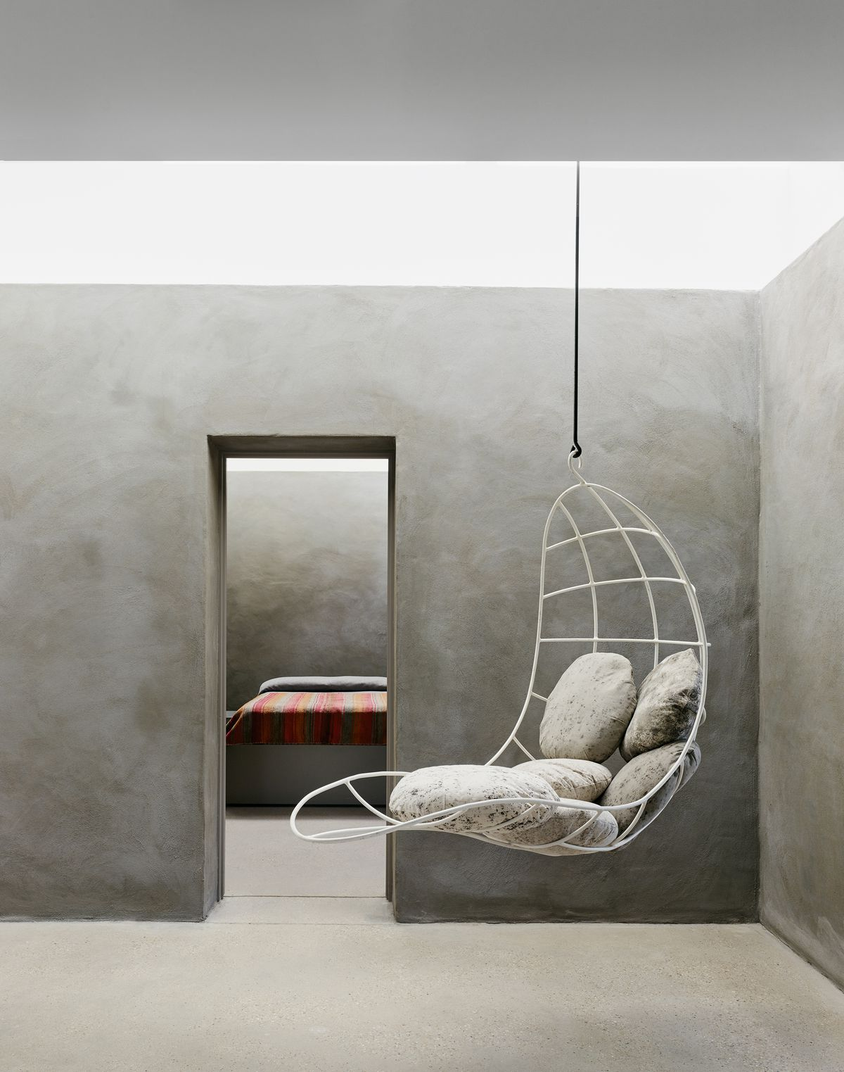 A vintage metal chair hangs from the ceiling. It's decorated by pillows crafted to look like stones. A bed is visible through the doorway. Walls are troweled gray concrete.