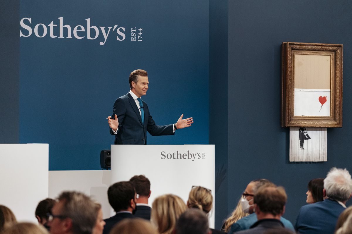 """In this handout photo provided by Sotheby's Auction House, the auction for Banksy's """"Love is the Bin"""" takes place in London, Thursday, Oct. 14, 2021. A work by British street artist Banksy that sensationally self-shredded just after it sold for $1.4 million has sold again for $25.4 million at an auction on Thursday."""