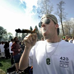 """FILE - In this April 20, 2009 file photo Garrett Kramer smokes marijuana during the 420 event on Norlin Quad at the University of Colorado in Boulder, Colo. The University of Colorado is closing its campus to outsiders on Friday and closing the Norlin Quad to prevent a 420 gathering. For years, the term """"420"""" was a kind of code. But the term, and the holiday, have become more mainstream as more attention has been focused on marijuana issues."""