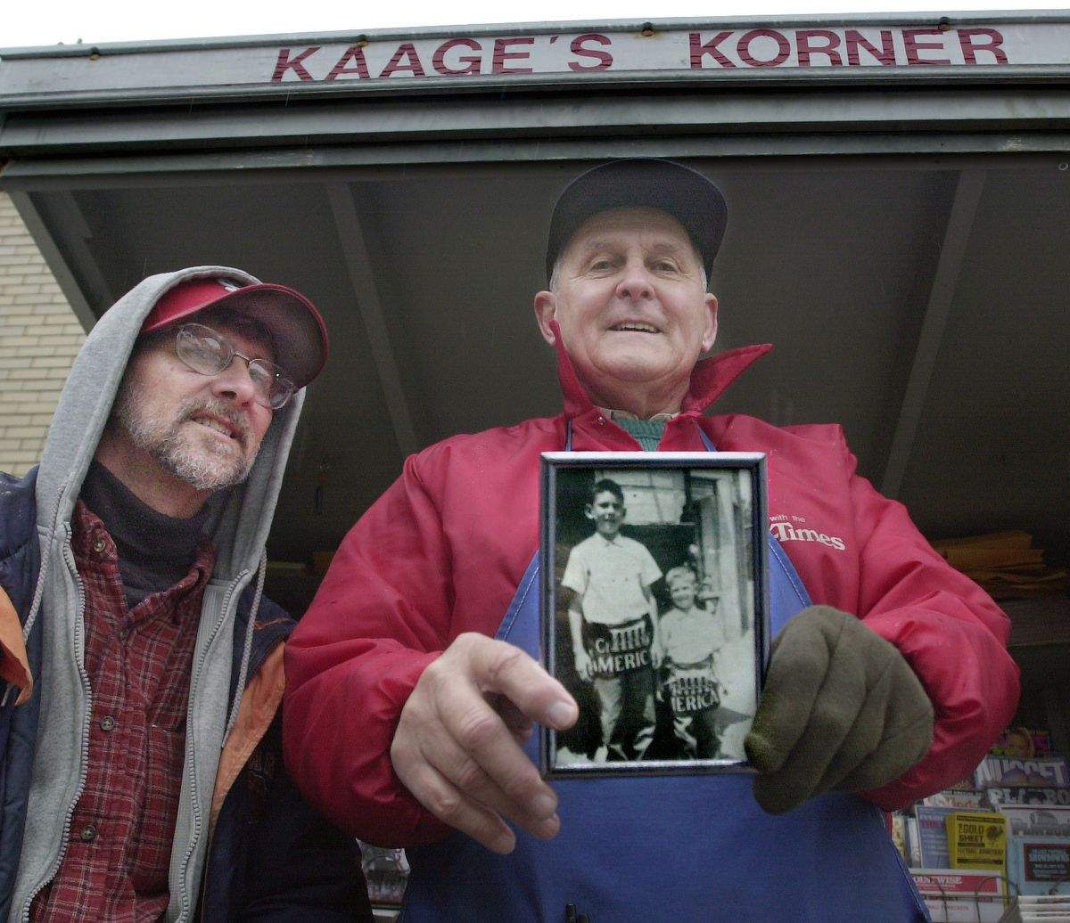 Irv Kaage Jr. (right) with his son Michael Kaage in November 2002 at Kaage's Corner, the Edison Park newsstand where at that point he'd been selling newspapers and magazines for over 60 years. That's Michael at age 5 and his older brother Irv Kaaage III in the photo the father's holding.