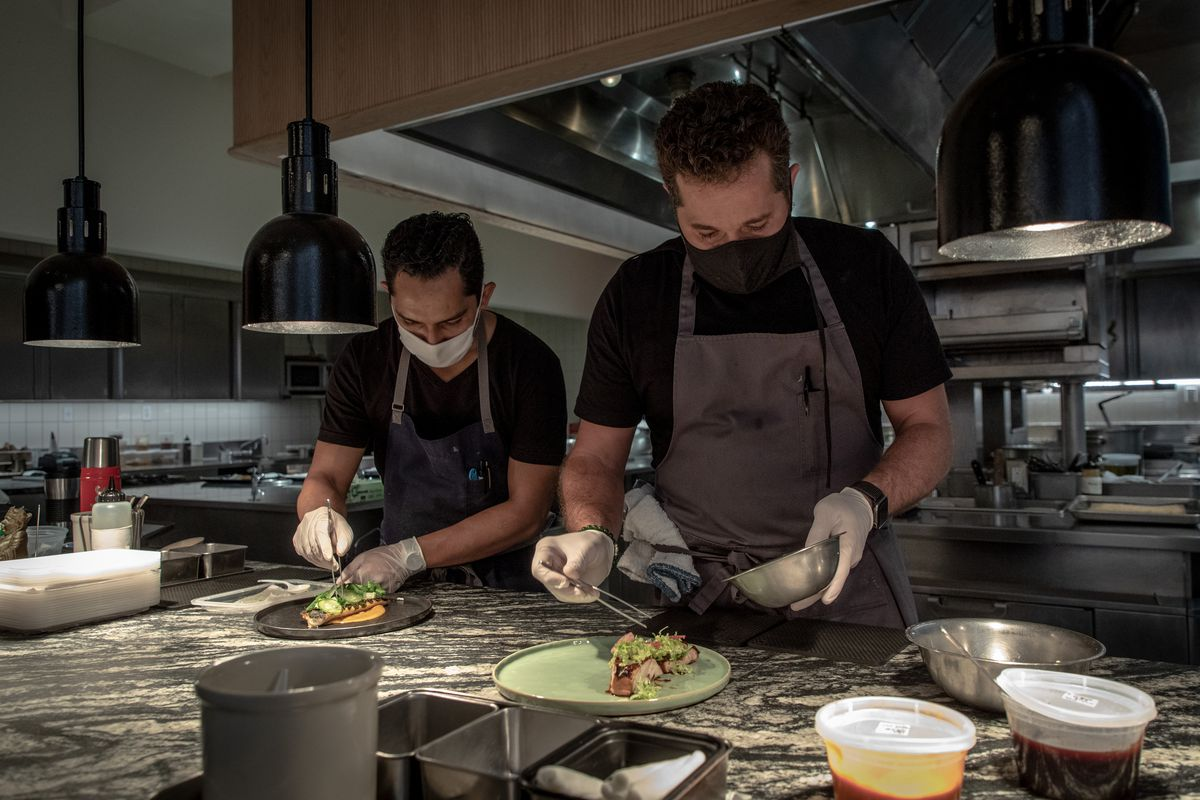 Two chefs in face masks work on food in a kitchen