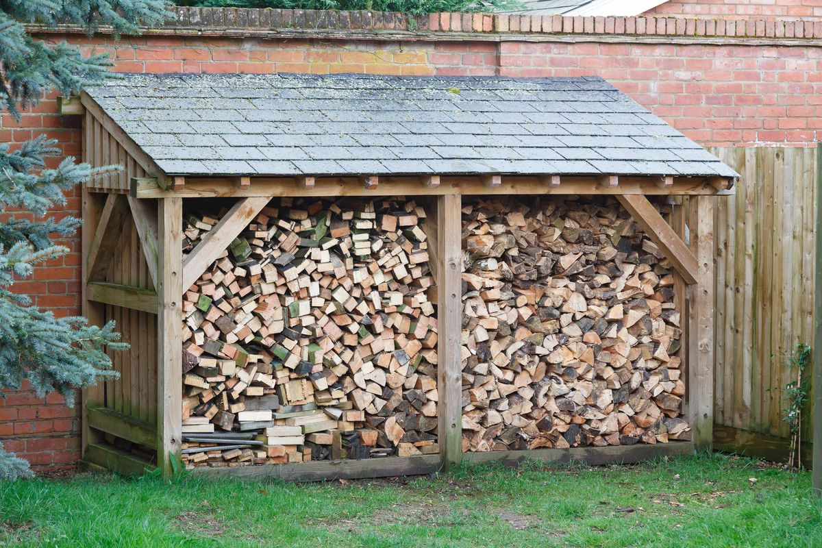 A covered lean-to structure containing firewood.