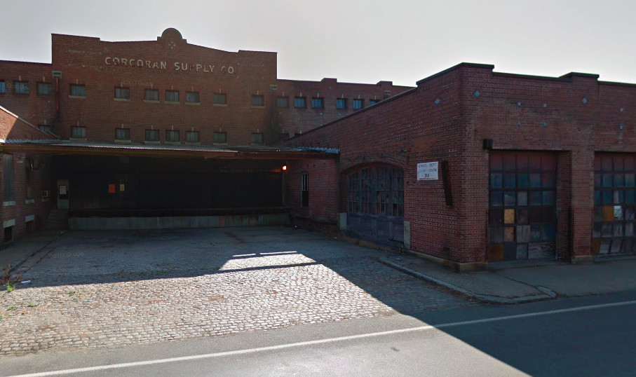 Street view of a large vacant brick building