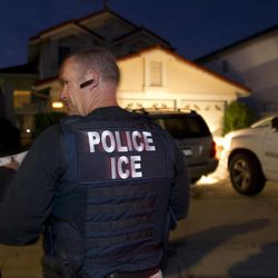 In this March 30, 2012 photo, an Immigration and Customs Enforcement (ICE) agent waits with other agents outside of the home of a suspect before dawn as part of a nationwide immigration sweep in San Diego. Federal officials say they arrested more than 3,100 immigrants convicted of serious crimes and fugitives in a six-day nationwide sweep. Officials at U.S. Immigration and Customs Enforcement say the sweep included every state and involved more than 1,900 of the agency's officers and agents.