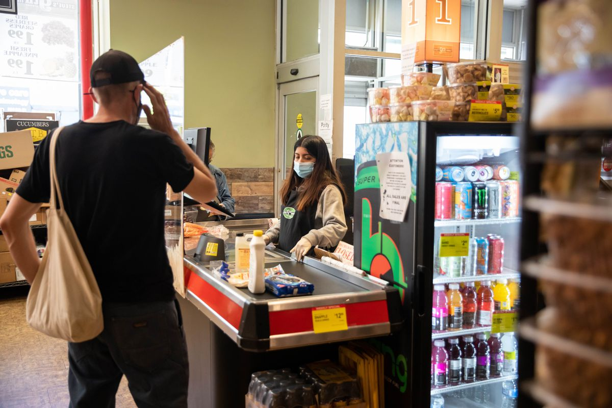 A masked cashier rings up groceries while a customer, seen from the back, waits.