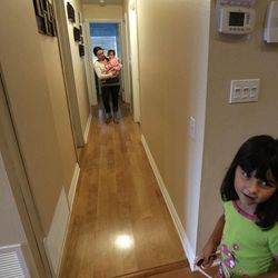 In this Sept. 26, 2012 picture, Domestic worker Alicia Wotherspoon carries Stella Widmann as she begins her day of work at the Widmann home in San Diego. Older daughter Luna Widmann looks on at right.