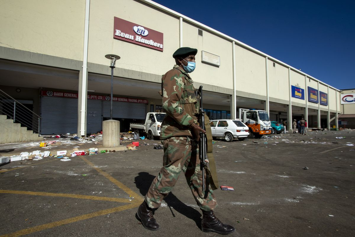 A soldiers patrol at a shopping centre in Soweto, Johannesburg Tuesday July 13, 2021. South Africa's rioting continued Tuesday with the death toll rising to 32 as police and the military struggle to quell the violence in Gauteng and KwaZulu-Natal provinces. The violence started in various parts of KwaZulu-Natal last week when Zuma began serving a 15-month sentence for contempt of court.