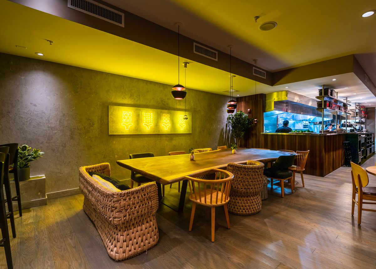 A heavy wooden communal table sits between yellow neon lights and the open kitchen at Maïz64.