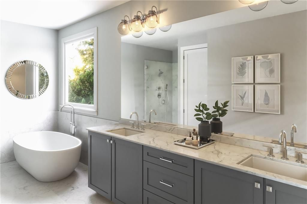 A white master bathroom with a very large mirror.