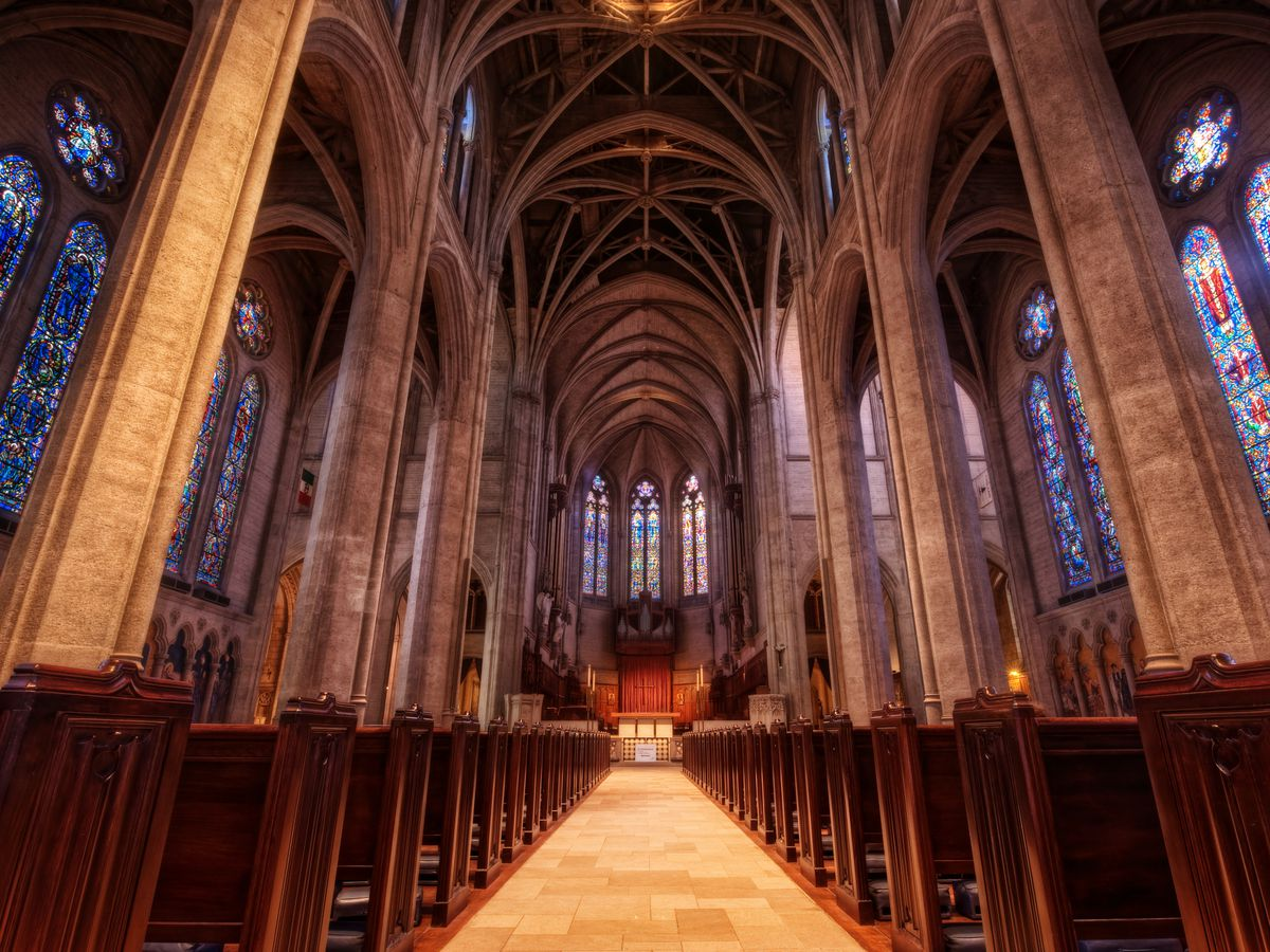 The interior of Grace Cathedral in San Francisco. There are pews, stained glass, and arched ceilings with exposed beams.