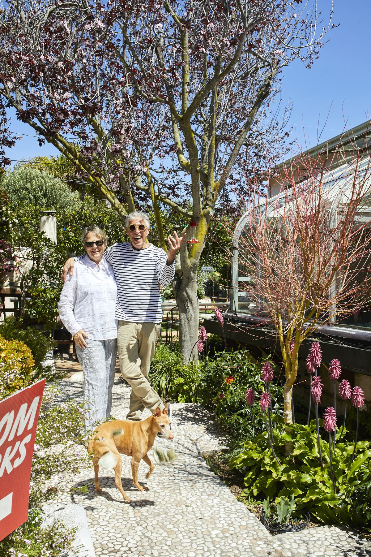 The homeowners, a man and a woman stand smiling under a tree. There is a dog standing in front of them.