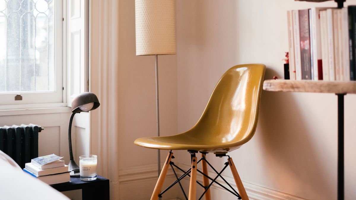 A mustard-colored chair sits in the corner of a room next to a tall, skinny lamp. To the right is a bookshelf, to the left is a small bedside reading lamp, a stack of books, and a candle in a glass jar.