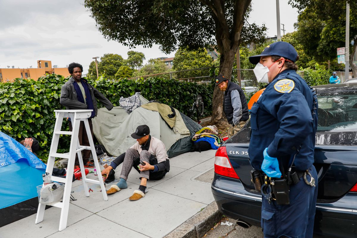 A police officer asks a group of homeless men to social distance themselves.