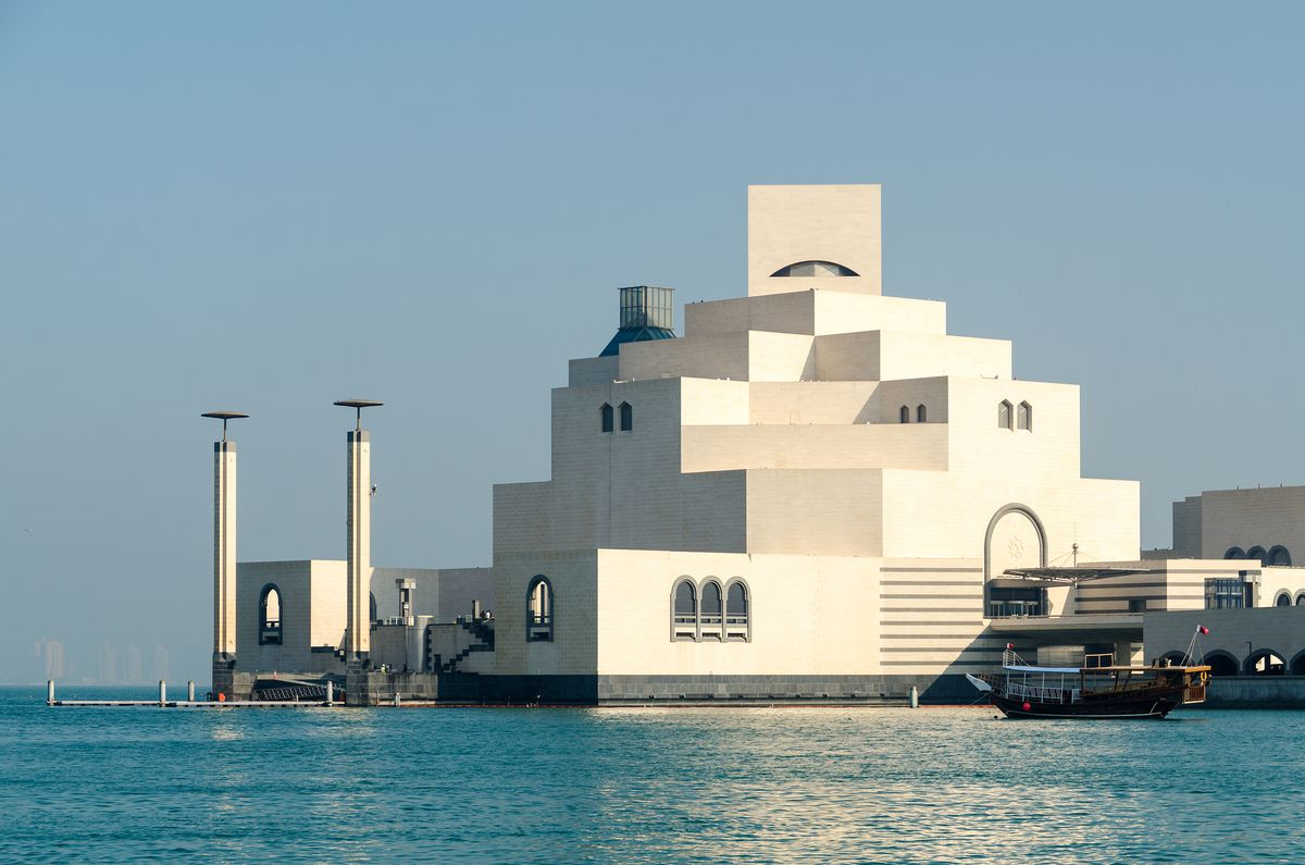 The exterior of the Museum of Islamic Art in Qatar. The facade is white and geometric with several terraces.