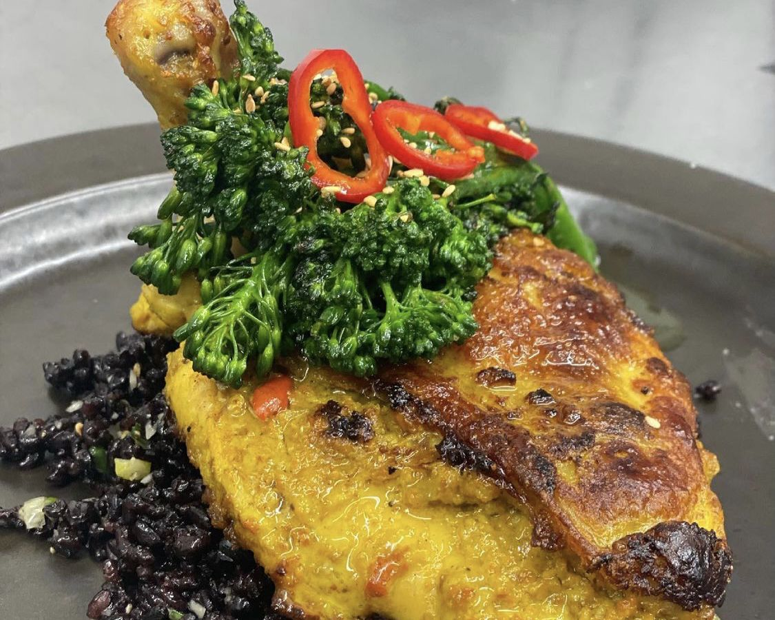 A large piece of chicken on a bed of saucy rice with sunflower seeds and broccolini