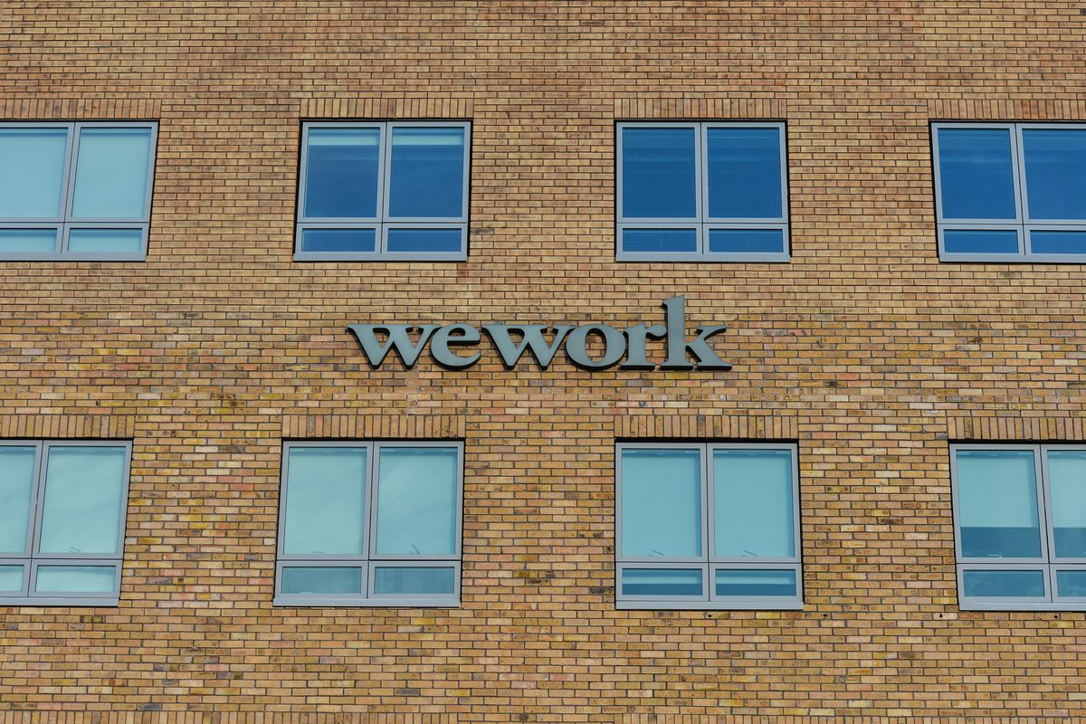 A WeWork sign on the side of a brick building in Dublin.