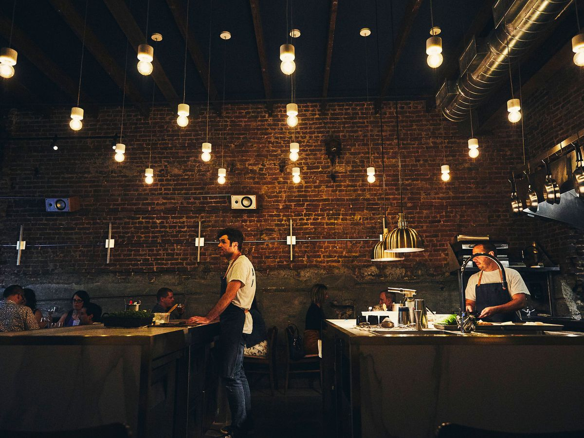 restaurant with brick wall and two cooks
