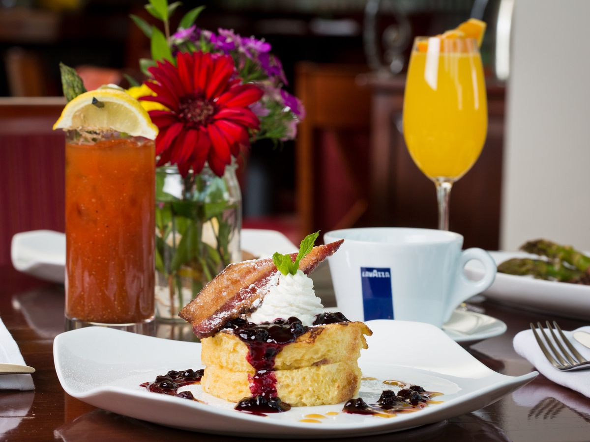 A stack of two thick French toast slices topped with mascarpone cream, a bacon slice, and berry compote, surrounded by table settings and brunch cocktails