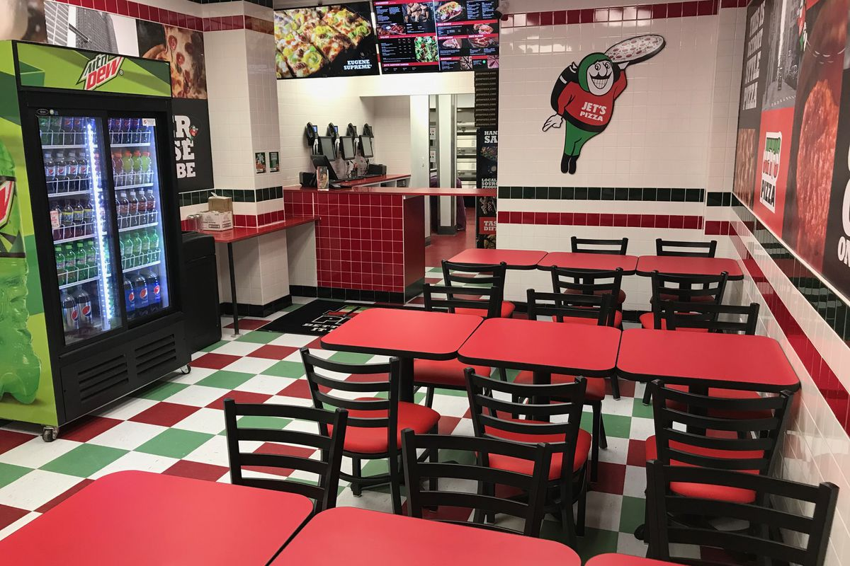 A dining room with red, green, and white tiles, red tables, a fridge, and a counter space