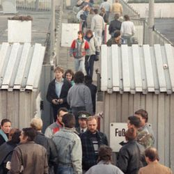 East and West Berliners pass the border crossing station in Berlin, Nov. 10, 1989, that connects East and West Berlin. Thousands of East Germans came to the west during the night following the opening of the borders from East Germany to the West.