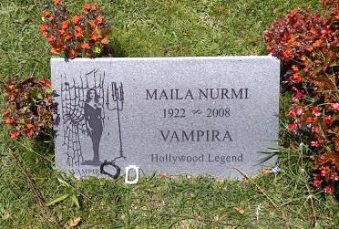 A grey gravestone. The words Maila Nurmi Vampira Hollywood Legend are written on the gravestone. There is a drawing of Vampira next to the words. There are two plastic models of fangs sitting against the gravestone. The gravestone is surrounded by plants