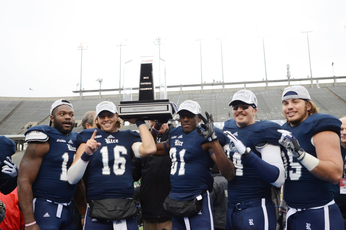 Former Owls Taylor McHargue and Donte Moore hoist the Conference USA Championship trophy