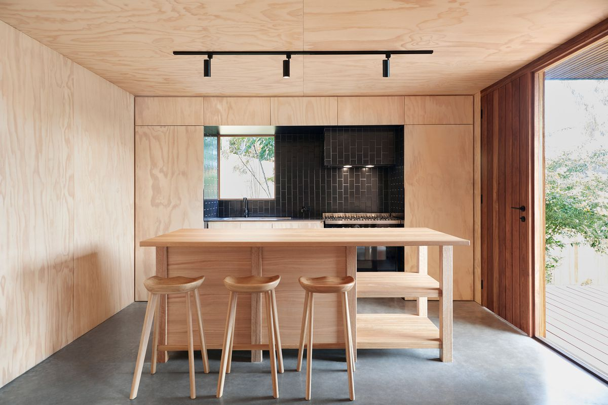 A kitchen with plywood walls, cabinetry, island, counters, bar seating, and a recessed area covered in black tiles, which contains the sink and oven. The room has two windows looking to the outside.