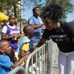 Cook County State's Attorney Kim Foxx shakes parade goers' hands during the Bud Billiken Parade Saturday.