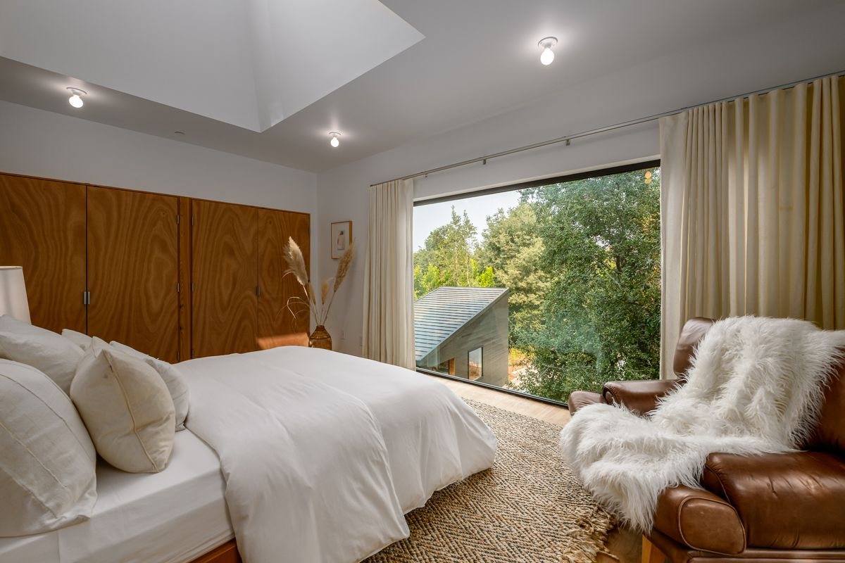 Bedroom with large window overlooking trees and a skylight.