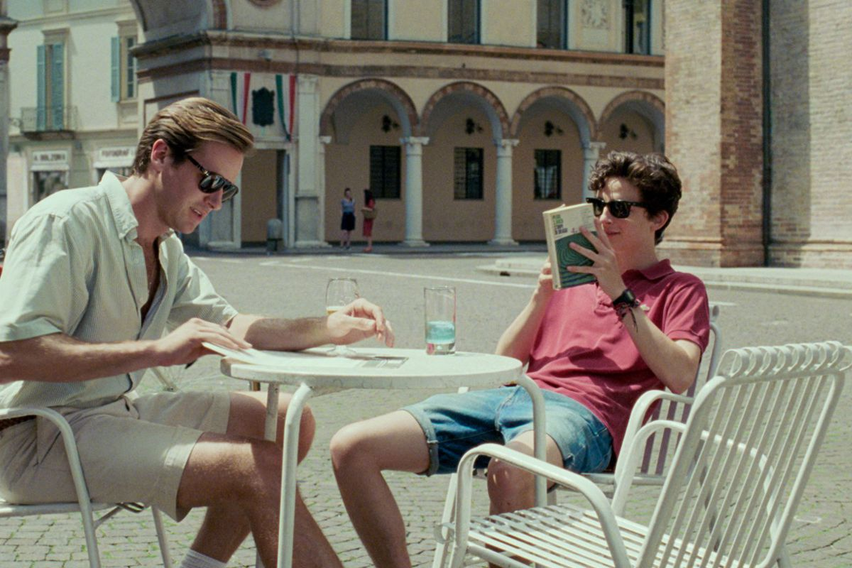 """Actors Timothée Chalamet and Armie Hammer sit at an outdoor cafe in the movie """"Call Me By Your Name."""""""