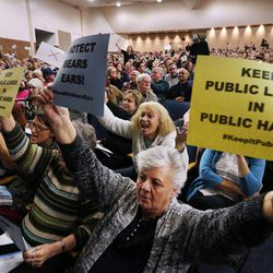 Carolyn Wiggins holds signs as Tami Sablan yells during a town hall meeting with Rep. Jason Chaffetz in Cottonwood Heights on Thursday, Feb. 9, 2017.