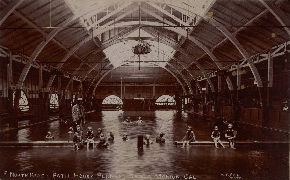 "Image of people, including children, swimming in the North Beach Bath House salt water plunge in Santa Monica, California. A sign that reads ""deep water"" hangs at the center of image above the indoor pool."