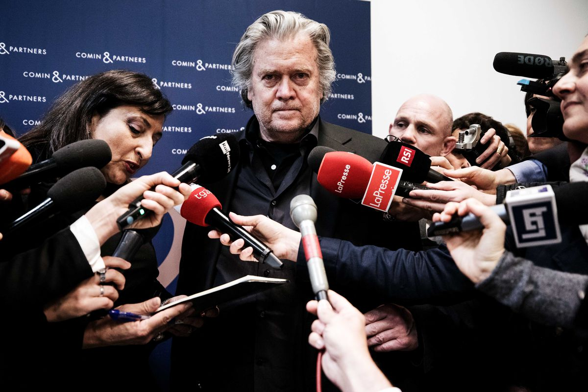 Steve Bannon surrounded by journalists with microphones.