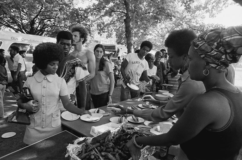 Members of the Black Panther Party stand behind tables and distribute free hot dogs.