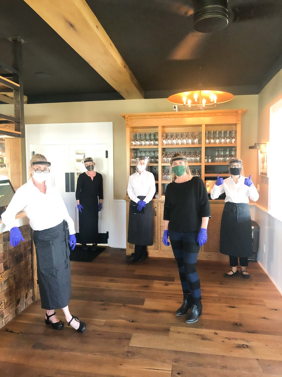 Five women stand at the entrance wearing PPE and aprons at Riverside Inn.