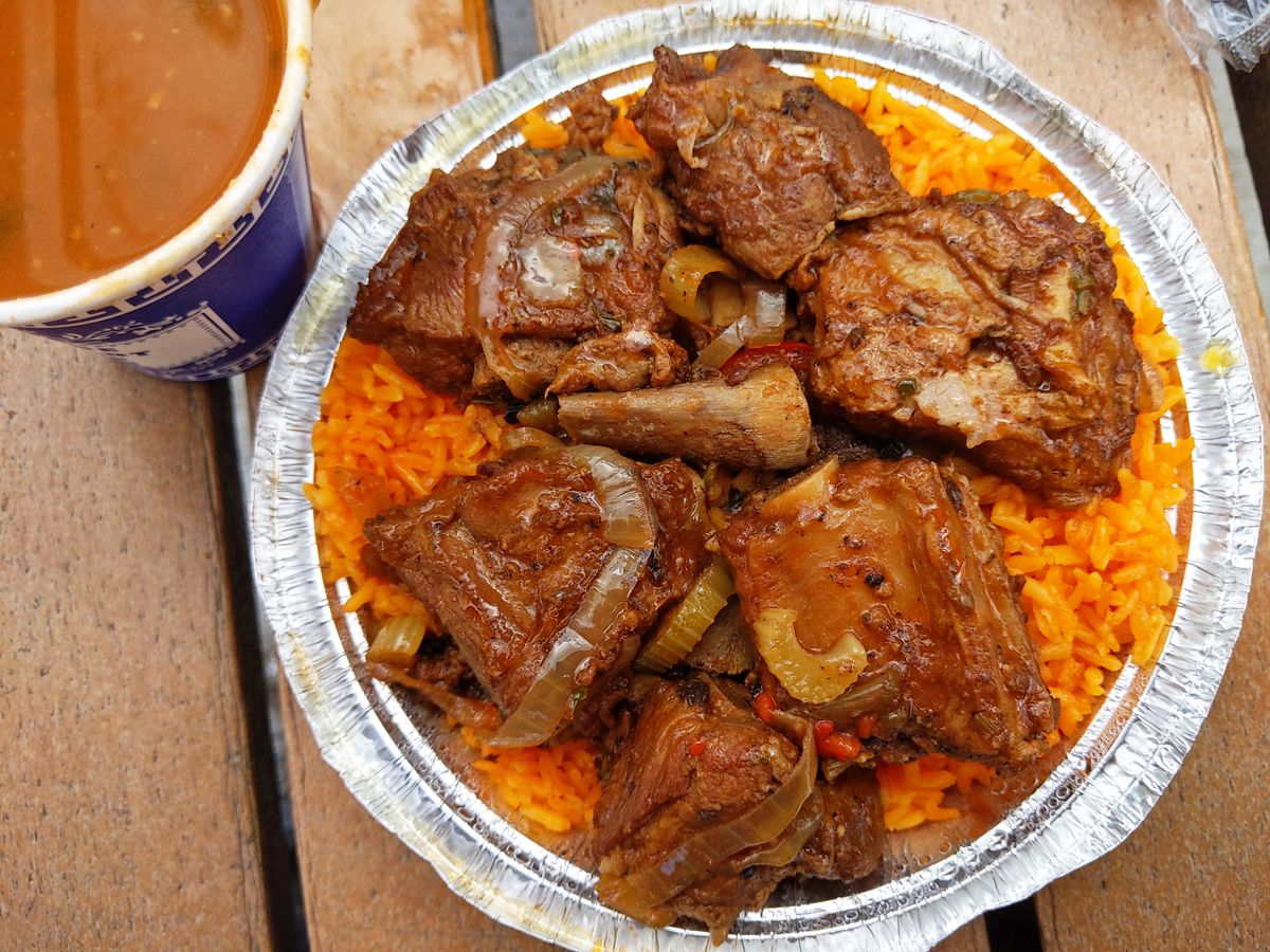 Orange rice with cross sections of stewed rib arranged on top in a round aluminum container, with a cup of beans partly visible in the corner.