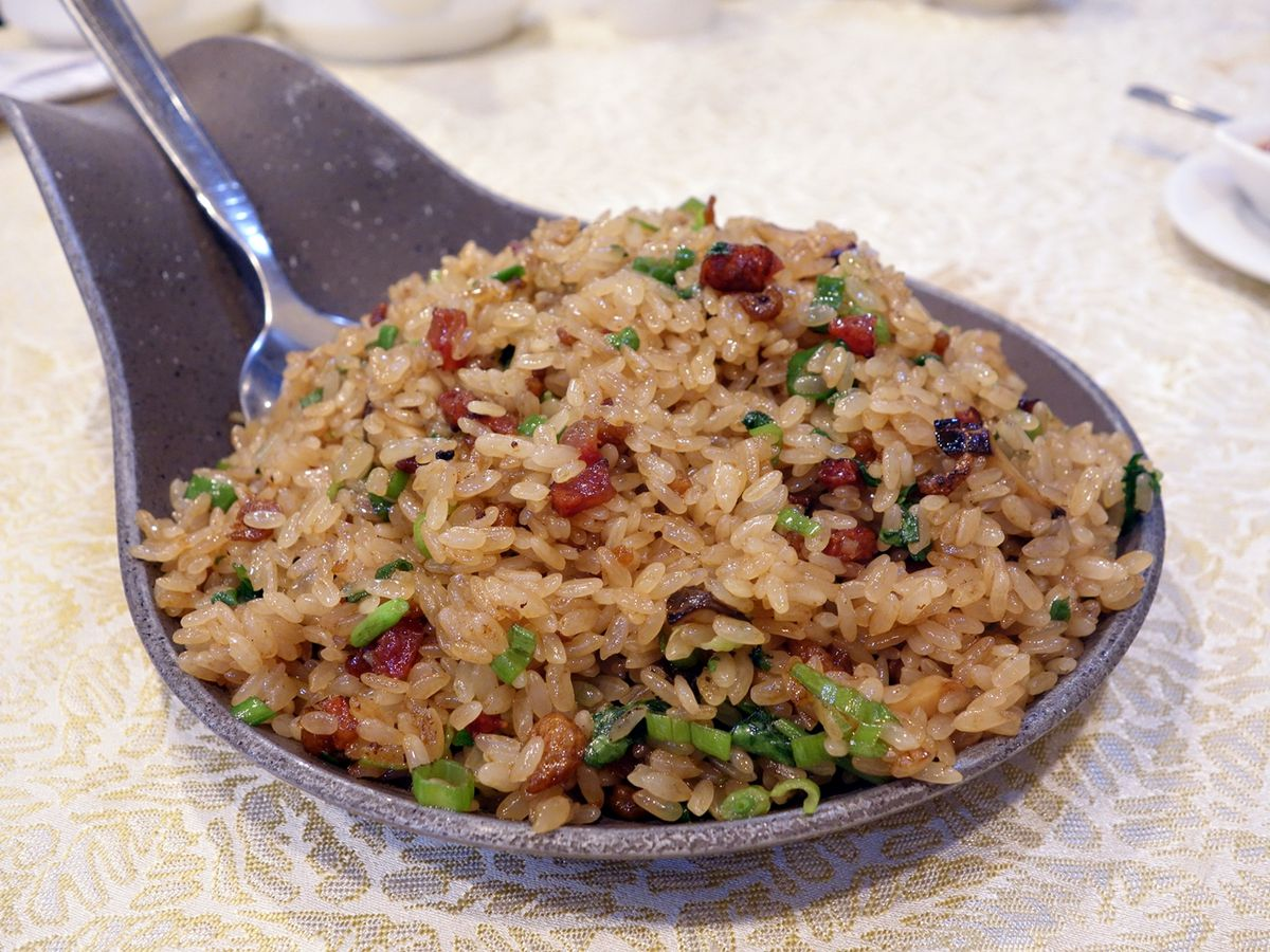 A large spoon-shaped dish filled with fried rice studded with bits of meat and greens, with a spoon sticking out one side