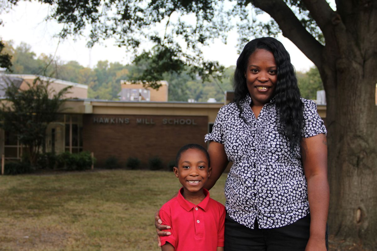 Alicia Tomlinson stands with her son, Jacobi, outside of Hawkins Mill Elementary School, where Jacobi is in the first grade. Tomlinson has applied to serve on her school's neighborhood advisory council.