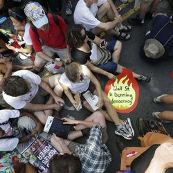 Demonstrators sit in an intersection during a protest march, Sunday, Sept. 2, 2012, in Charlotte, N.C. Demonstrators are protesting before the start of the Democratic National Convention.