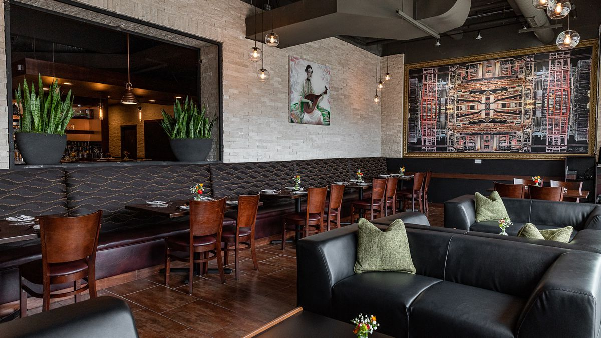 The dining room at Savant has dark wavy patterned upholstered banquettes, leather couches, and art on the walls.