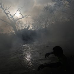 A competitor wades across a water obstacle during the Tough Guy Challenge on January 27, 2013 in Telford, England.
