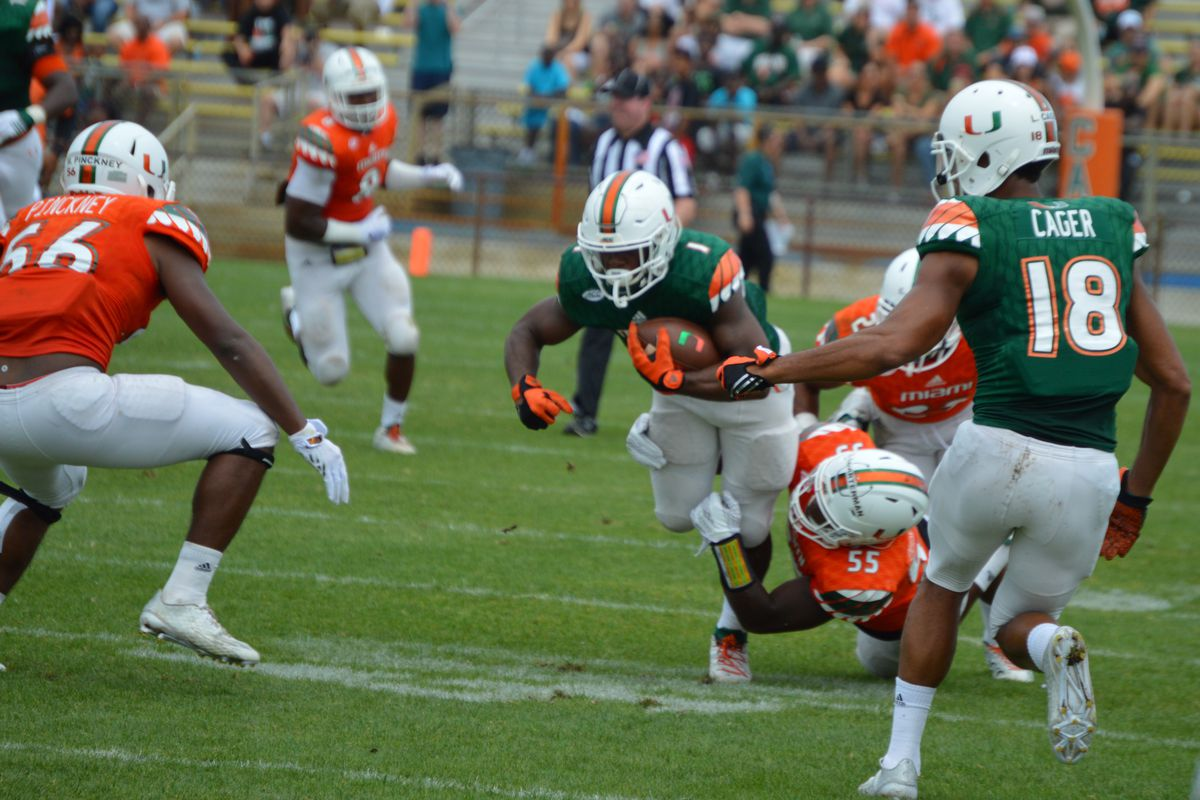 Linebacker Shaquille Quarterman tackles running back Mark Walton as fellow freshman weakside linebacker Micheal Pickney and receiver Lawrence Cager look on during the Miami Hurricanes 2016 Spring Game.